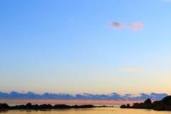 天空和云彩在沿海水域上镇静表面  免版税库存图片
