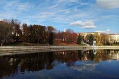 天空和树的美丽的景色在城市,反映在水 免版税库存图片