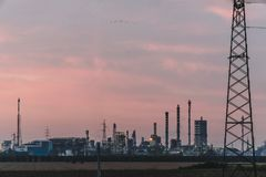天空日落背景的,有平衡背景的天空的石油化工厂工业工厂 在现代的意大利北部工作 免版税库存图片