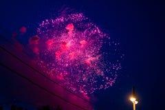 天空是与桃红色烟花、导线和灯岗位 免版税库存图片