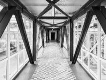 天空桥梁或转折在大厦之间在化工厂在地面高空横穿保存的时间上的工作者黑色的 图库摄影