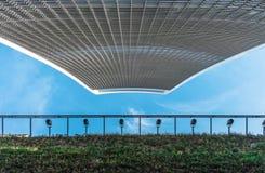 天空用一个绿色门面和蓝天从下面观看的庭院摩天大楼 免版税图库摄影