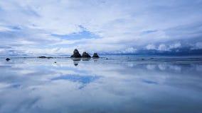天空的反射,岩石和云彩在风平浪静浇灌 免版税库存照片