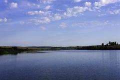 天空的湖与蓝色反射和青山 免版税库存图片