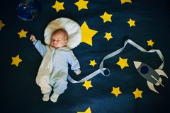 天空的背景的睡觉的男婴宇航员 免版税库存照片
