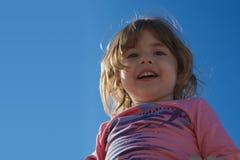 天空的背景的笑的小女孩 免版税库存照片