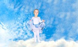 天空的逗人喜爱的小女孩 免版税库存照片