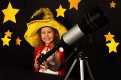 天空看守人服装的愉快的女孩有望远镜的 免版税库存图片