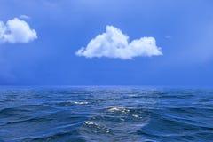 天空背景与一朵唯一云彩的在水或ocea反射了 免版税图库摄影