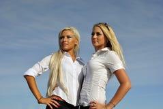 天空背景的二个白肤金发的女孩 免版税库存图片