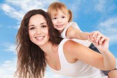 天空背景的愉快的母亲和女儿 库存照片