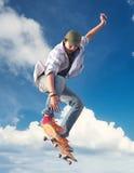 天空背景的溜冰者 库存图片