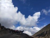 天空蔚蓝、白色厚实的云彩、山、马和登山人 库存图片