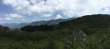 天空蔚蓝、空的山、山在距离,绿色和许多白色云彩在天空 免版税图库摄影