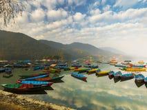 天空蔚蓝反射在水中,不同的五颜六色的小船在湖 免版税库存照片