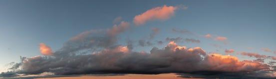 天空蔚蓝和剧烈的云彩全景照片在日落 在云彩的日落光 免版税库存照片