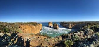 天空蔚蓝,岩石海岸,白色浪花 免版税库存图片