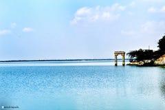 天空覆盖湖水被放弃的桥梁结构 库存照片
