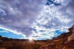 天空覆盖蓝色黄色太阳日落山岩石自然强光光芒 库存图片