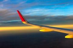 天空覆盖飞行日落移动的平面翼 免版税库存照片