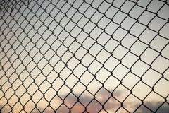 天空通过铁丝网篱芭 弄脏背景,链接笼子看法的关闭  免版税库存图片