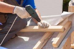 天窗设施 盖屋顶的人建造者工作者紧固一个木粱的用途skrewdriver 免版税图库摄影