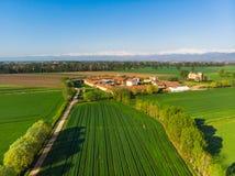 天线在有积雪覆盖的阿尔卑斯的意大利绿色乡下从上面培养了领域,农村农场在背景,在晴朗的收获中 库存图片