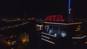 天线:一个现代大厦的屋顶的霓虹红色题字旅馆在夜城市 交通汽车是下的在路 股票录像