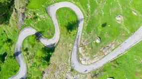 天线:冠上在绕山路的看法飞机尾旋下在意大利阿尔卑斯、横穿绿色草甸和牧场地高山谷的, 库存图片