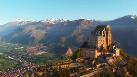 天线:在老中世纪修道院的寄生虫飞行在山上面,多雪的阿尔卑斯的惊人的背景栖息日出的 Sacra di圣 股票录像