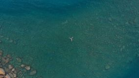 天线:漂浮大海表面上的妇女,游泳在透明地中海,上面下来观看,暑假概念 库存照片