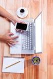 天花板使用智能手机和膝上型计算机的女性手 免版税库存照片