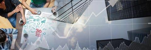 天花板在桌附近的千福年的队用咖啡和与城市的企业乱画提供经费给图表tr 图库摄影