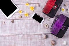 天花板精华在时尚博客作者反对 时尚Python snakeskin提包顶视图,智能手机,片剂 免版税库存照片