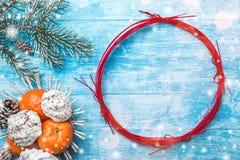 天蓝色的木背景 冷杉绿色结构树 果子用普通话和甜点 红色圈子圣诞节消息或新年 图库摄影