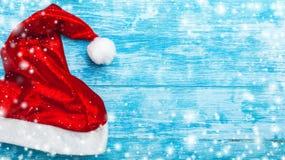 天蓝色的木背景 绿色冷杉,骗局 圣诞节贺卡和新年 圣诞老人` s消息的空间 圣诞老人` s盖帽 免版税库存图片