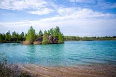 天蓝色的河,与绿色树的多小山海岸的图象 图库摄影