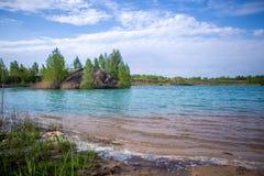 天蓝色的河,与绿色树的多小山海岸的图象 库存图片