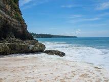 天蓝色的海滩用印度洋清楚的水峭壁的晴天A视图的在巴厘岛,印度尼西亚 库存图片