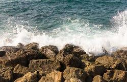 天蓝色的海白色波浪是残破的关于岸褐色石头希腊 免版税库存照片