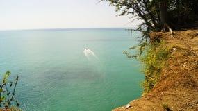 从天蓝色的海水的海岸的小白色小船航行对天际的 免版税库存图片