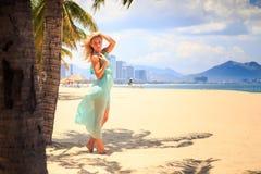 天蓝色的白肤金发的女孩用在头上的手在海滩的棕榈附近 库存图片
