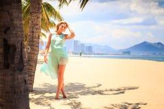 天蓝色的白肤金发的女孩用在头上的手在海滩的棕榈附近 库存照片