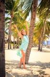 天蓝色的白肤金发的女孩用在头的手在海滩的棕榈中 免版税库存照片