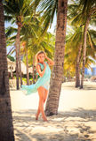 天蓝色的白肤金发的女孩用在头的手在海滩的棕榈中 库存图片