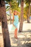 天蓝色的白肤金发的女孩用在头的手在海滩的棕榈中 免版税图库摄影