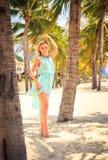天蓝色的白肤金发的女孩用在头的手在海滩的棕榈中 图库摄影