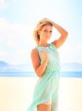 天蓝色的白肤金发的女孩调查在海滩的照相机 库存图片