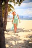 天蓝色的白肤金发的女孩调查在海滩的照相机 免版税库存图片