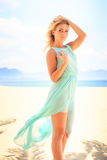 天蓝色的白肤金发的女孩调查在海滩的照相机 库存照片